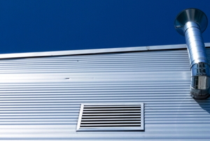 the side of a metal building with a vent and chimney