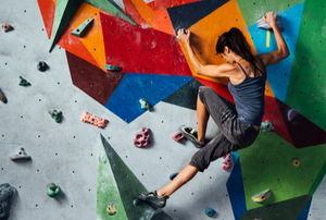 woman climbing wall with protruding surfaces
