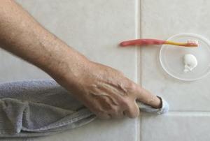A man sealing the grout between floor tile.