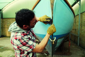 A boater cleaning the bow of an old sailing boat.