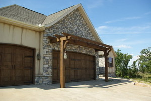 A wood pergola or arbor in front of a house over the garage door.