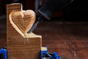 A Dremel tool carving a heart out of a piece of wood.