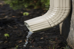 A downspout next to a house draining water into the ground.