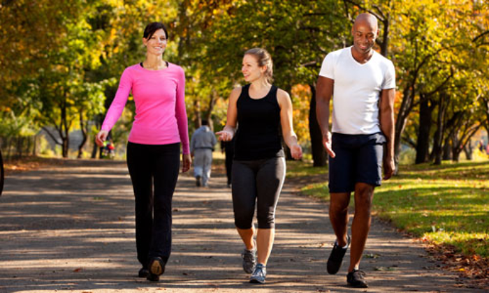 three people walking in a park