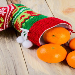Christmas stocking with oranges rolling out.