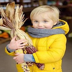 Child holding Indian corn