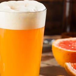 Two glasses of grapefruit cider next to sliced grapefruits