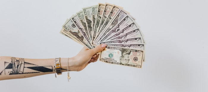 hand holding a fan of paper money