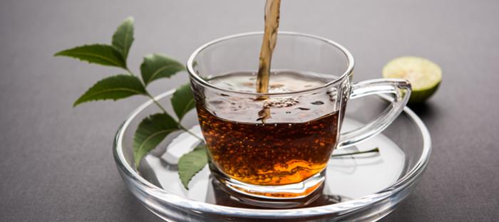 Cup of neem tea on glass saucer