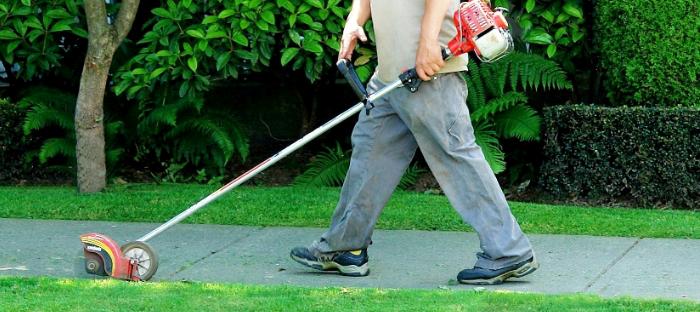 Person edging lawn along sidewalk