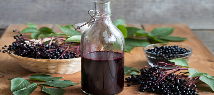 Elderberries in bunched next to bottle of berry juice