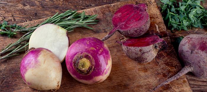 Turnip bulbs, stems, and leaves on a wood cutting board
