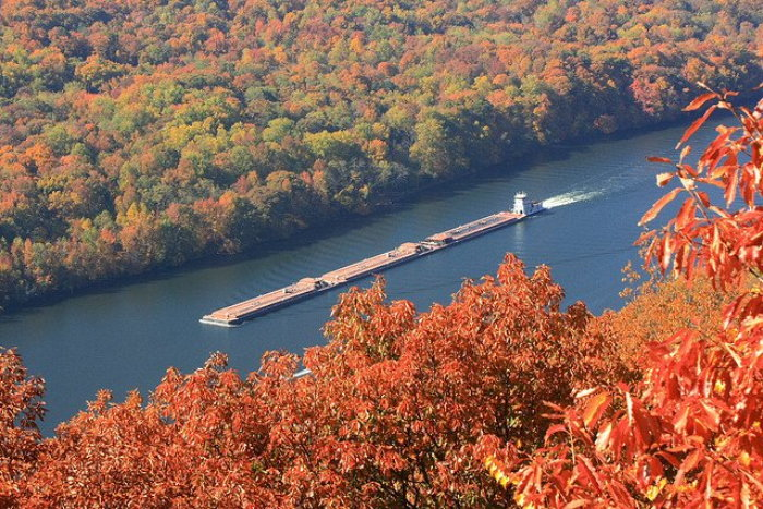 colorful fall foliage and barge on the river