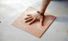 a hand pressing a tile down on the ground
