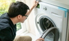 A man looks at a dryer.