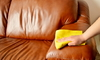 person wiping a leather couch