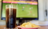 A TV in the background with a football game on, and soda and chips in the foreground.