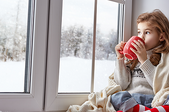 A girl sits by a large window to watch the snowfall