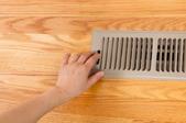 a metal floor register placed on a vinyl plank wood floor