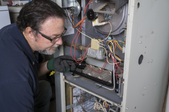 man working on a furnace with the panel off