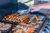 an open grill with a stack of hot dogs and other meats cooking.