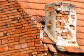broken brick and mortar chimney on brick building with terracotta roof