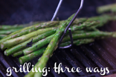 A bunch of asparagus on an electric grill with tongs picking them up and the words