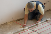 man on his hands and knees working on a floor