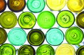 An assortment of colorful wine bottles lit from behind.