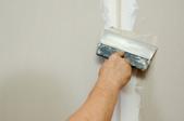 A man smooths drywall.
