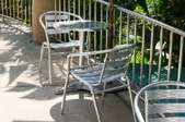 A small chair and table set of aluminum furniture.
