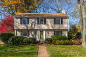 A colonial home in autumn with trees surrounding it.