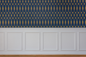 blue and gold wallpaper above waincotting on a wall