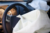 An airbag coming out of a steering wheel.