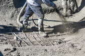 worker spraying concrete mixture to form the base of a pool