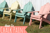 A row of pastel adirondack chairs with the words