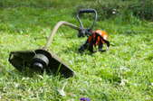 A weed eater lying on the grass, unused.
