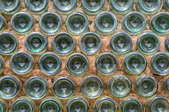 A wall made of glass bottles, filled between with cement.
