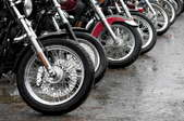 A row of parked motorcycles showing the front tires.