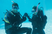man proposing to woman underwater in scuba gear