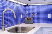 a kitchen with blue tile backsplash