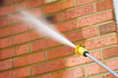 Spraying a brick wall with water from a hose