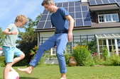 father and son in front of active solar powered house