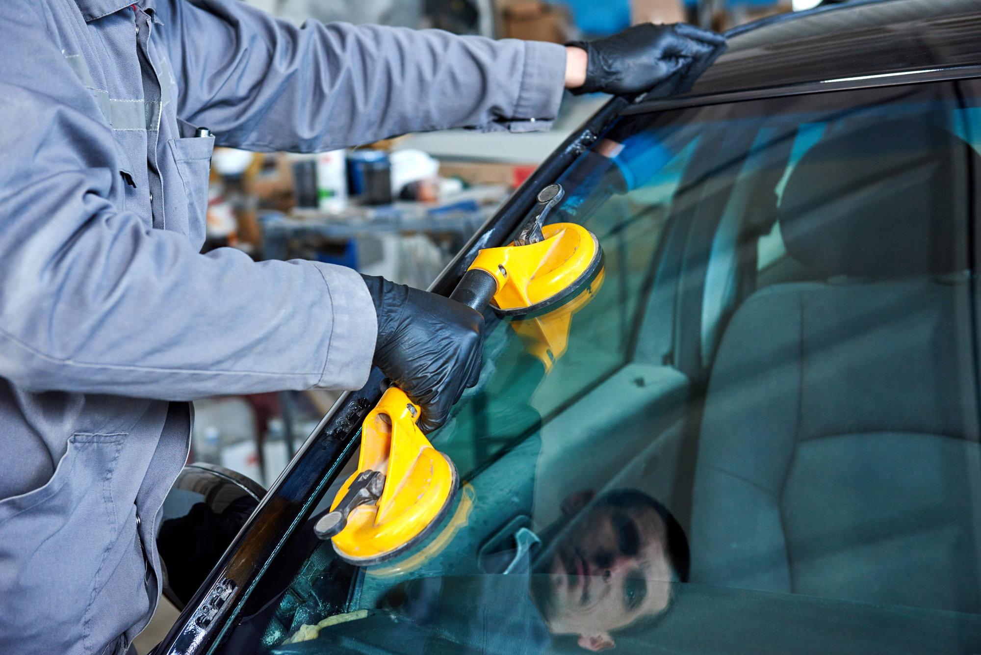 Механик заменяет лобовое стекло автомобиля.
