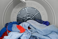 The interior view of a dryer with clothes in it.