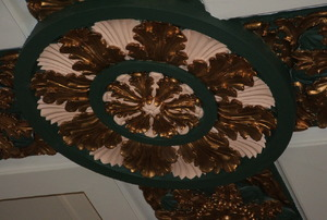 A green- and gold-painted ceiling medallion.