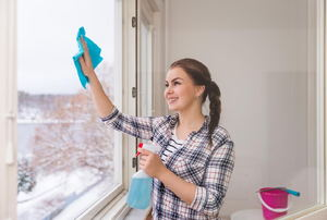 A woman cleaning a window with a spray bottle and rag.