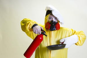 Someone in a yellow suit wearing a chef hat and holding a fire extinguisher and a pan.