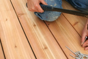 a person nailing new wooden planks onto a deck