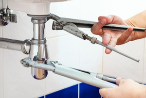 two hands adjusting valves under a sink using tools